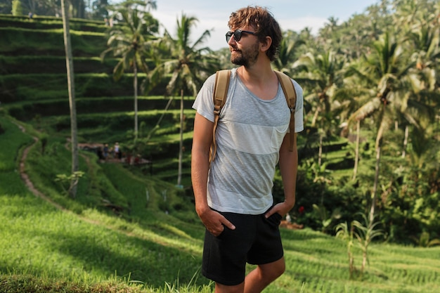 バリ島のライズテラスを歩いてバックパックでハンサムな旅行人の屋外のポートレート。 無料写真