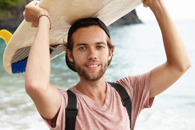 Открытый портрет красивого молодого серфера в снэпбэке, задом наперед позирующего на фоне синего моря, держащего белый бодиборд над головой и счастливо улыбающегося Бесплатные Фотографии