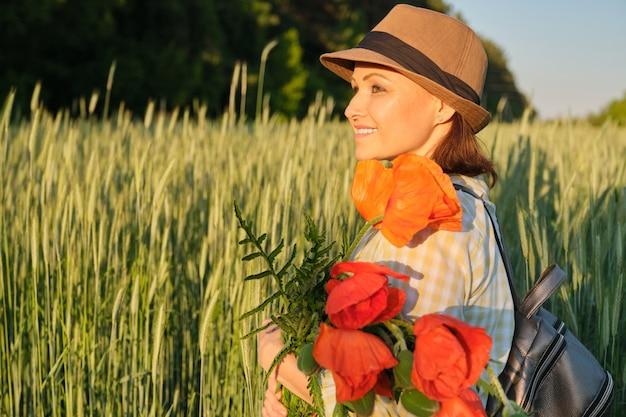 赤いケシの花の花束と幸せな成熟した女性の屋外のポートレート Premium写真