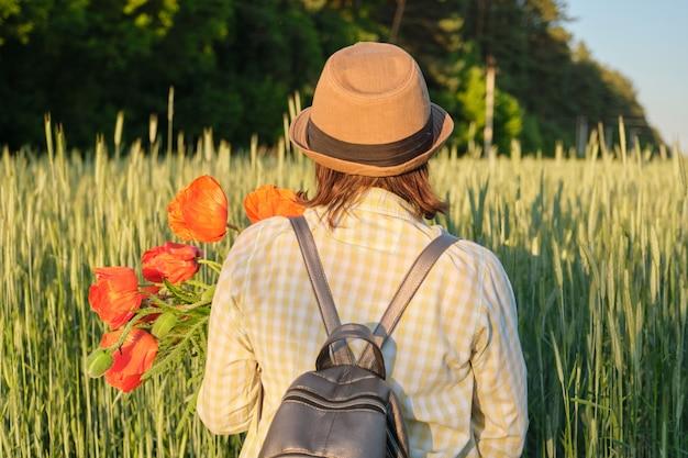 赤いケシの花束と幸せな成熟した女性の屋外のポートレート Premium写真