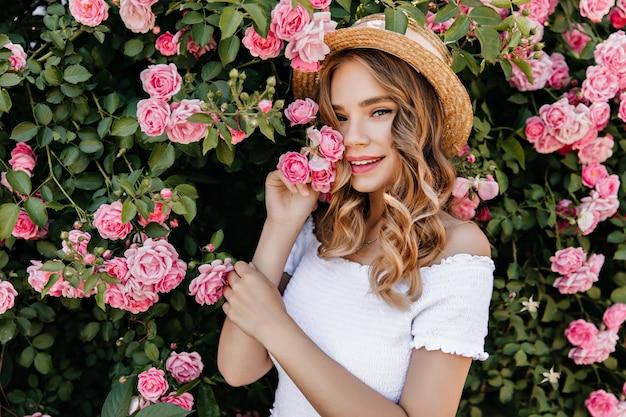 自然にポーズをとって幸せな白人の女の子の屋外の肖像画。美しいバラの茂みの近くに立っているウェーブのかかった髪のリラックスした女性の写真。 無料写真