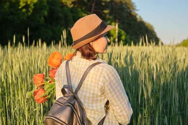 ケシの花束を持つ成熟した女性の屋外のポートレート Premium写真