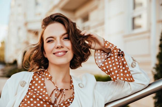 ぼやけた街で満足しているブルネットの女性の屋外の肖像画。トレンディなヘアカットで白人の魅惑的な女の子のショット。 無料写真