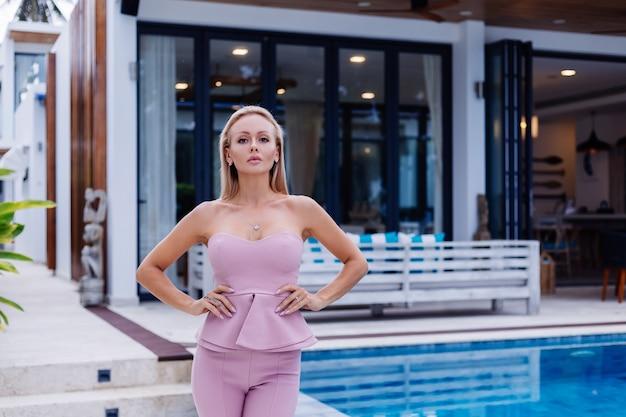 Открытый портрет стильной европейской женщины в розовом модном костюме возле виллы Бесплатные Фотографии