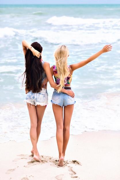 Outdoor ritratto di bella ragazza con i capelli castano scuro in posa con gli occhi chiusi su sfocatura dello sfondo del mare. attraente giovane donna bionda con il tatuaggio del braccio divertendosi con un amico durante le vacanze estive. Foto Gratuite