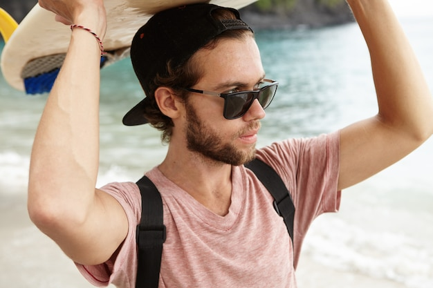 Outdoor portrait of stylish young surfer in sunglasses holding surfboard on his head and looking at blue sea with confident and determined expression Free Photo