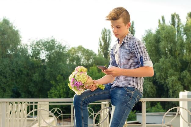 Outdoor portrait of teenage boy with bouquet of flowers. Premium Photo