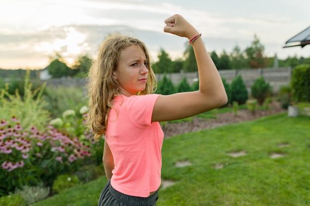 Outdoor portrait teenage girl flexing her muscles Premium Photo