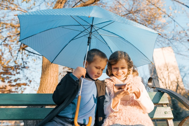 Outdoor portrait of two smiling children of boy and girl, sitting under an umbrella on bench in the