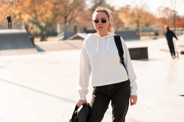 Outdoor portrait of young beautiful woman with a ponytail and sunglasses, with a backpack on his shoulders, dressed in a white sweater, near the sportsground. white hoodie Premium Photo