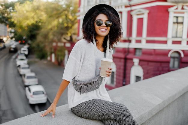 Открытый положительный образ улыбающегося довольно черная женщина в белом свитере Бесплатные Фотографии