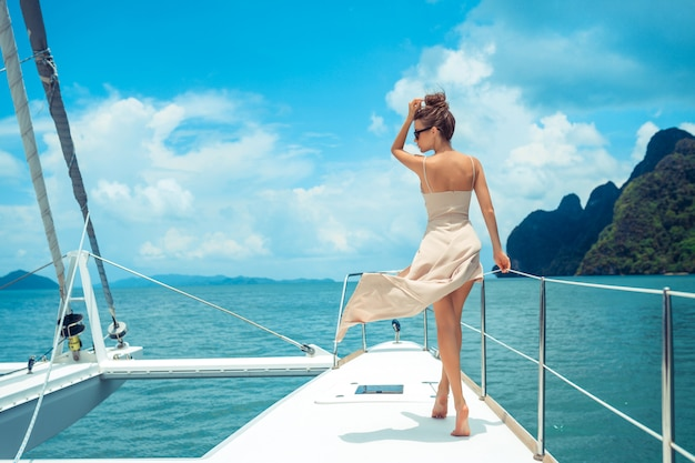 Outdoor shot of adorable young woman in a beige dress standing on edge of yacht, looking to beautiful nature landscape during trip. happy woman enjoying summer travel. Premium Photo