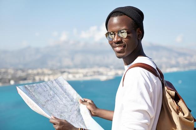 Ripresa in esterni di atrractive alla moda dall'aspetto turistico dalla pelle scura che studia la mappa cartacea nelle sue mani, indossando occhiali da sole e cappello, in piedi sulla piattaforma turistica, contemplando il fantastico mare azzurro sottostante Foto Gratuite