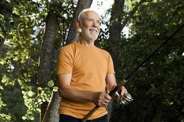 Outdoor shot of attractive unshaven senior caucasian male holding spinning rod cast in river waters, smiling with anticipation, waiting for fish to be hooked, flare sun and green trees in Free Photo