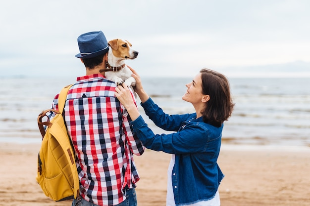 Outdoor shot of friendly family and their favourite dog come to sea Premium Photo