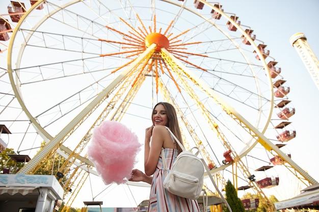 Colpo all'aperto di felice giovane donna bruna con i capelli lunghi che indossa un abito romantico e zaino bianco, in piedi sulla ruota panoramica in una calda giornata estiva, tenendo lo zucchero filato e sorridente ampiamente Foto Gratuite