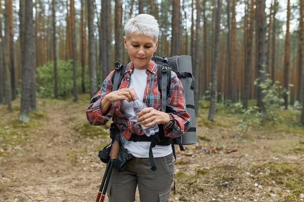 松の木に立ち向かい、国立公園での長い疲れ果てたトレッキング中に自分自身をリフレッシュし、水のボトルを開けるバックパックを運ぶアクティブな白人の中年女性の屋外ショット 無料写真