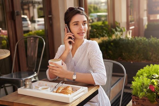 여름 테라스에 테이블에 앉아 Coffe를 마시는 우아한 옷을 입고 매력적인 젊은 검은 머리 아가씨의 야외 촬영, 전화 통화를하면서 신중하게 옆으로보고 무료 사진