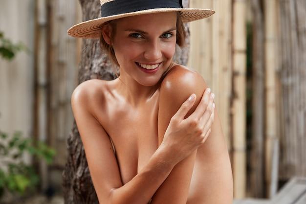 完璧なスリムなボディを持つ格好良い笑顔の女性の屋外撮影は、裸であることを隠し、スタイリッシュな夏の帽子をかぶって、一人でポーズをとっています。 無料写真