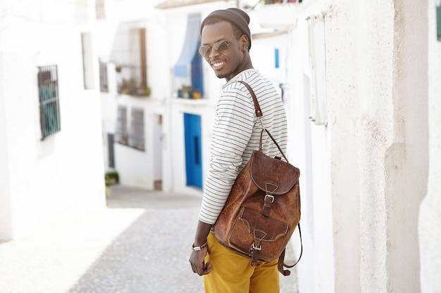 Открытый выстрел красивый счастливый молодой афро-американский мужчина путешественник с кожаным рюкзаком, стоя у бетонной стены на узкой улице во время осмотра достопримечательностей в курортном городе во время его летних каникул Бесплатные Фотографии