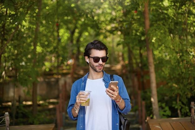 緑の公園の路地を歩いて、レモネードを飲みながら彼のスマートフォンでメールをチェックしている青いシャツとサングラスの素敵な若い黒髪の男の屋外ショット 無料写真