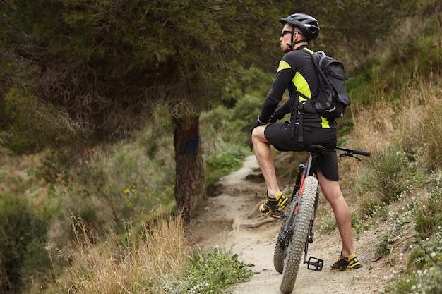 Открытый снимок мужского велосипедиста, одетого в велосипедную одежду и защитное снаряжение, стоящего на тропинке в лесу со своим черным электрическим велосипедом и смотрящего вокруг в поисках лучшего лучшего маршрута для катания на горных велосипедах Бесплатные Фотографии
