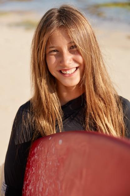 心地よい見た目の明るい髪の女性の屋外ショットは、歯を見せる笑顔、心地よい表情、ウェットスーツを着て、サーフボードを持っています 無料写真