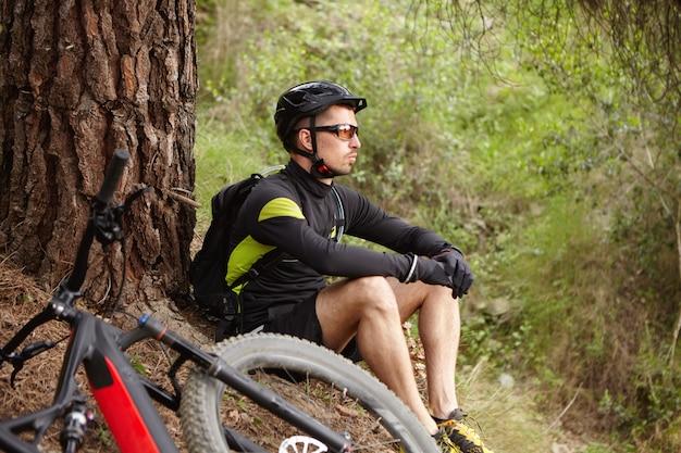 壊れた電動自転車が地面に横たわって大きな木の下に座って、友人が彼を助けるのを待っているスポーツ服、ヘルメット、眼鏡を着ている悲しい、不幸な若いサイクリストの屋外撮影 無料写真
