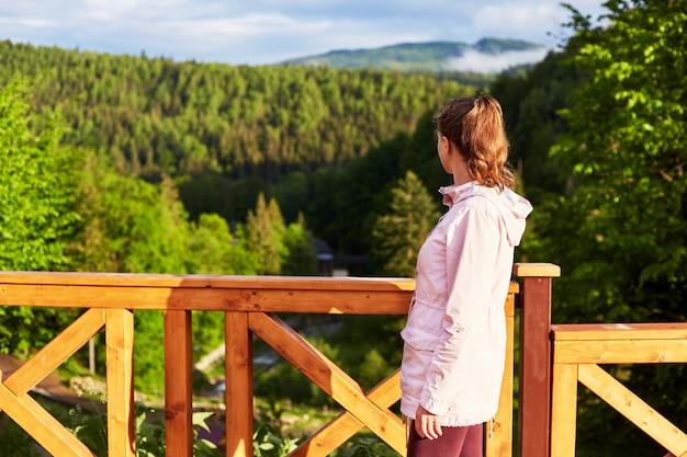 木製の橋や山側のバルコニーの屋外撮影、緑の森と日当たりの良い丘、立っている若いスリムな女性のプロファイル Premium写真