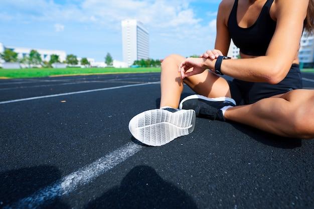 競馬場で走っている若い女性アスリートの屋外ショット。トレーニングセッションの実行中のプロのスポーツウーマン。 Premium写真