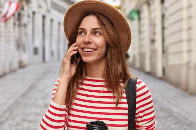 Colpo esterno di felice viaggiatore caucasico parla su smart phone in roaming, gode di tariffe economiche per la comunicazione, si trova sulla strada Foto Gratuite
