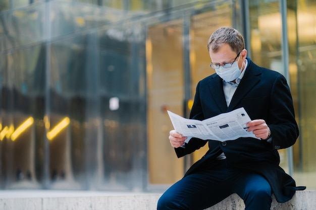 Outdoor shot of serious man boss takes break after walking, reads newspaper, wears spectacles for good vision, medical mask to protect himself from viruses, finds out news about spreading coronavirus Premium Photo
