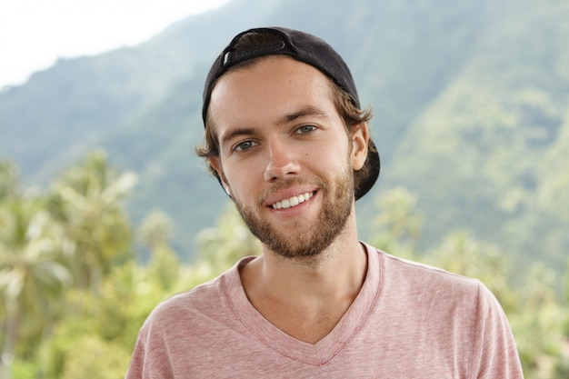 Outdoor shot of young caucasian man with beard relaxing in open air, surrounded by beautiful mountain setting and rainforest Free Photo