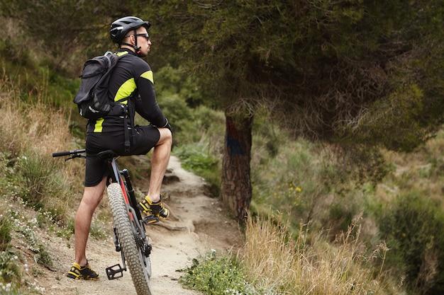 Colpo all'aperto di giovane maschio europeo che indossa abbigliamento da ciclismo, casco e occhiali Foto Gratuite