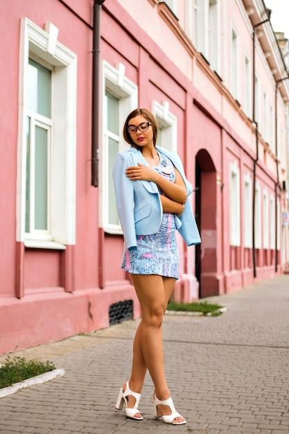 上品なミニドレスとスカイブルーのジャケットを着て、エレガントな魅力のセクシーな女の子を屋外のストリートスタイルのファッションルック 無料写真