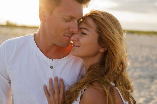 Ritratto all'aperto del primo piano di estate di giovani belle coppie alla moda sulla spiaggia. Foto Gratuite