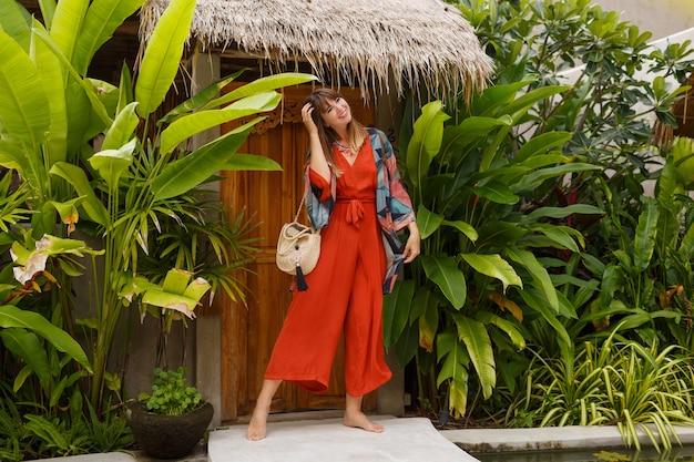 На открытом воздухе фото моды лета великолепной женщины в обмундировании boho, позирующем в тропическом роскошном курорте. полная длина. тропические растения. Бесплатные Фотографии