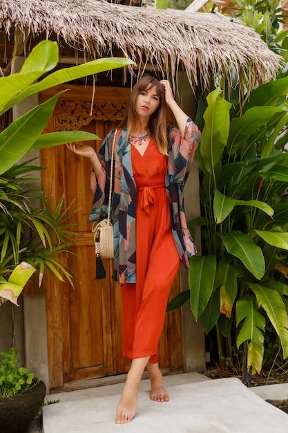 トロピカルラグジュアリーリゾートでポーズをとる自由奔放に生きる衣装でゴージャスな女性の夏の屋外ファッション写真。 無料写真