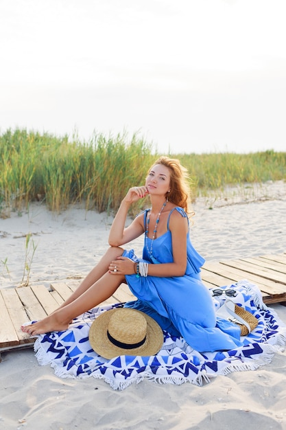 Outdoor summer image of romantic woman relaxing on sunny beach in blue dress. Free Photo