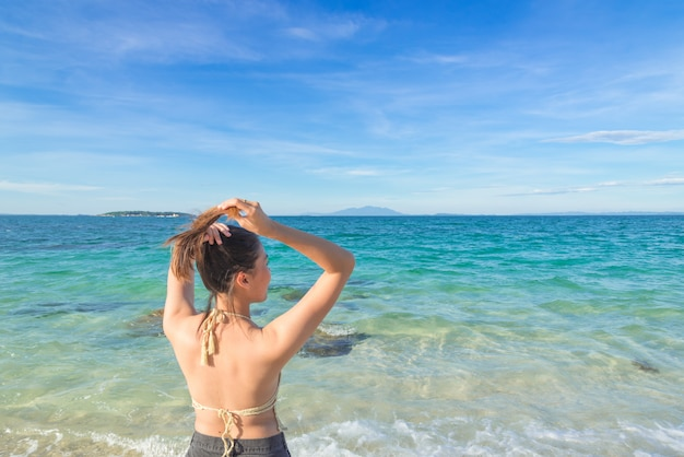 Outdoor summer portrait of young pretty woman looking to the ocean at tropical beach Premium Photo