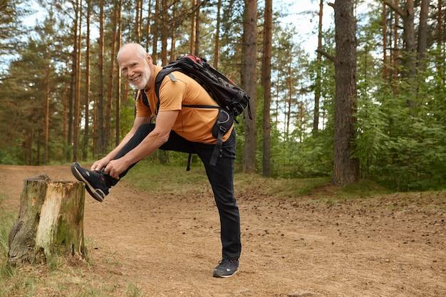 Colpo estivo all'aperto di maschio anziano in forma sana con zaino in posa nella foresta con il piede sul mozzo, allacciare i lacci delle scarpe da ginnastica, prepararsi per una lunga salita, fare escursioni con un sorriso felice Foto Gratuite