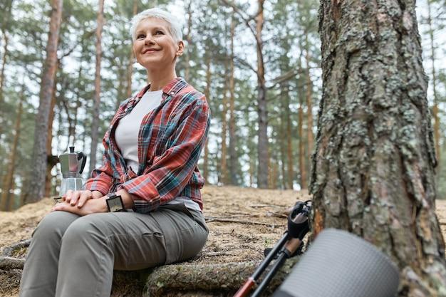 木のそばに座って、やかんでお茶のために水を沸騰させ、楽しい表情をして、美しい自然を賞賛し、鳥が歌い、幸せそうに笑っている魅力的な冒険的な中年女性の屋外夏の景色 無料写真