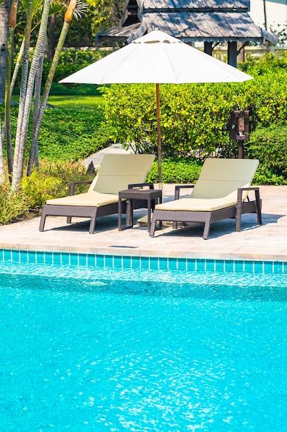 레저 여행 휴가를위한 우산과 의자 주위에 바다 바다 해변이있는 야외 수영장 무료 사진