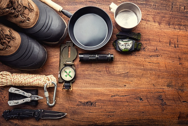 Outdoor travel equipment planning for a mountain trekking camping trip on wooden background Premium Photo