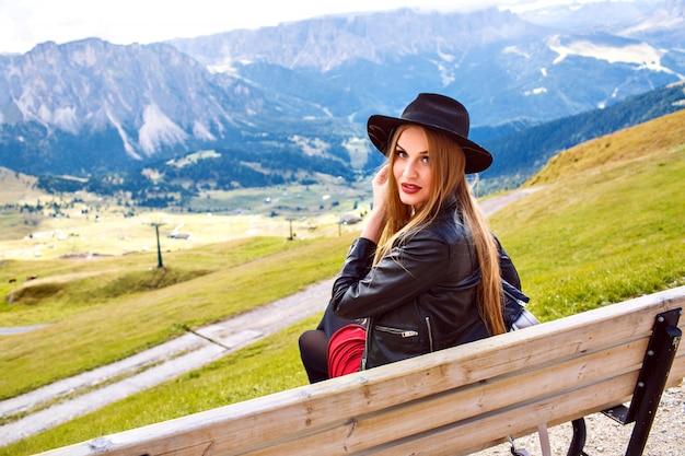 アルプスの山々、豪華な旅行の素晴らしい景色を手で見せて、マウンテンリゾートのベンチに座っているスタイリッシュな女性の屋外旅行の画像。 無料写真