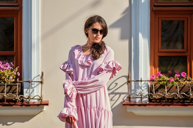 Outdoor urban portrait of young beautiful stylish girl in oversized pink dress Premium Photo