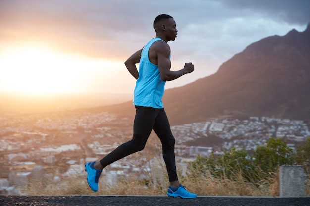 Outdoor view of active young male jogger covers long destiantion ealy in morning at dawn, runs over mountains view, has biceps, dressed in activewear, breathes deeply, enjoys summer weather. Free Photo