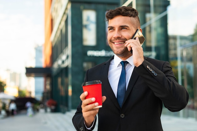 Outdoors business man drinking his coffee and talking on the phone Free Photo