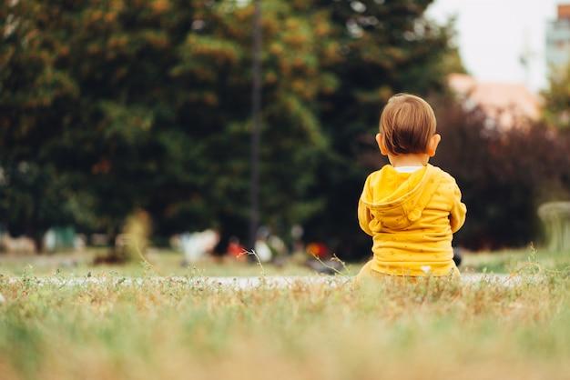 Задний взгляд маленького ребёнка сидя самостоятельно outdoors на траве. dof. копировать пространство Premium Фотографии