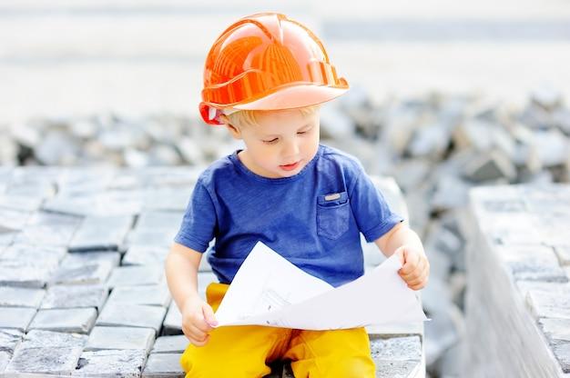 Портрет милого маленького построителя в защитных шлемах читая чертеж конструкции outdoors. l Premium Фотографии